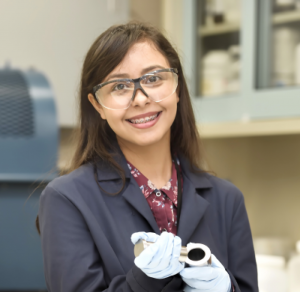 Eleana Cintron - young female student in a science lab coat holding mechanical tools and wearing gloves and safety glasses.