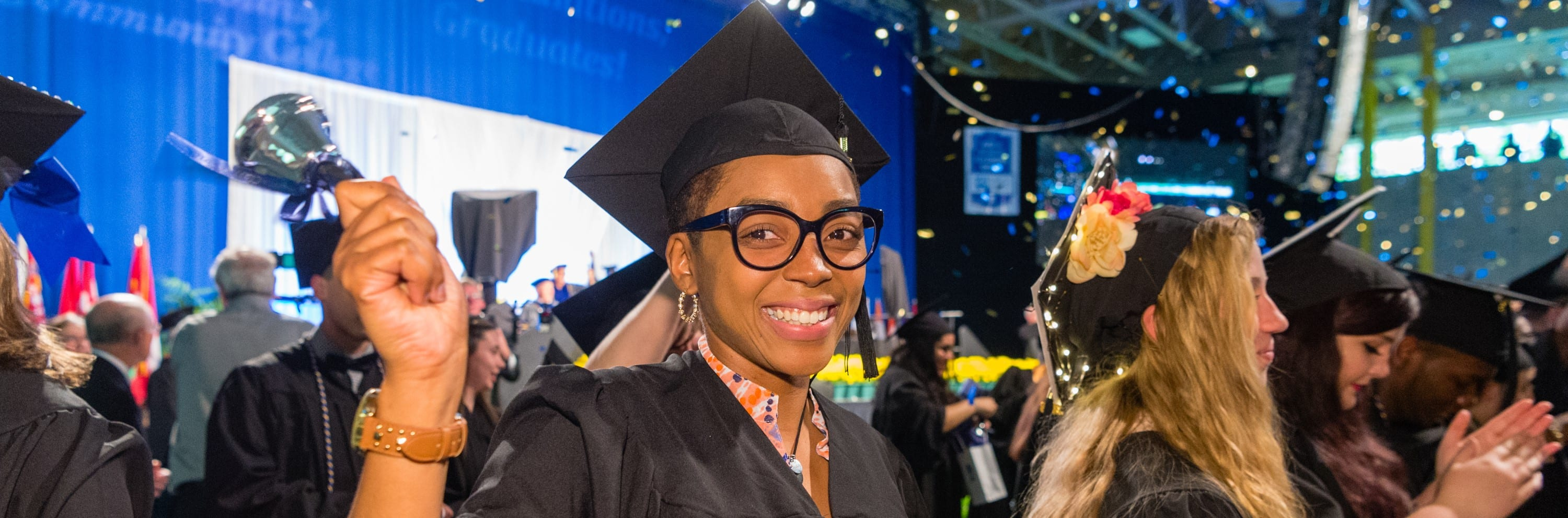 Girl in graduation regalia. African american wearing glasses and smiling. She is ringing a small bell. The commencement festivities in the background.