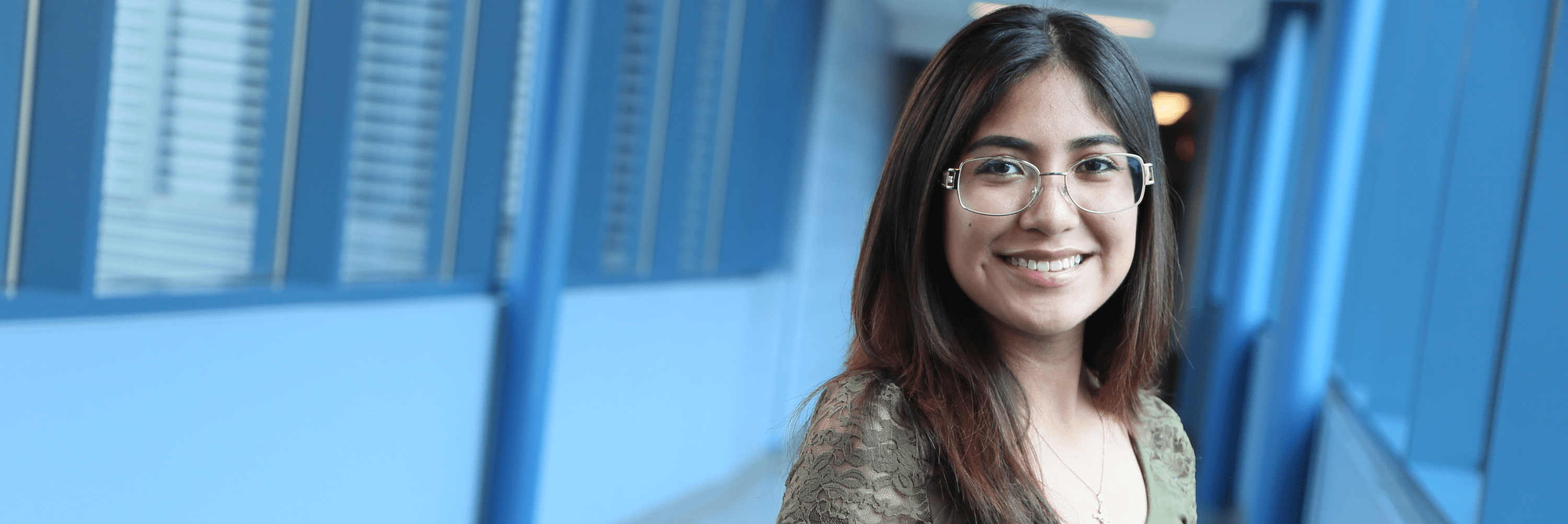 Young hispanic woman with glasses standing in a hallway smiling