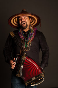 Terrance Simien performs with a large hat.