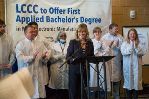 LCCC President Marcia Ballinger stands at a podium surrounded by students in lab coats.