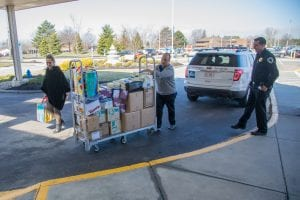 LCCC security officers and hospital employees wheel boxes of supplies on a cart.