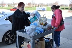 Two women load a cart with donated food for Commodore Cupboard.