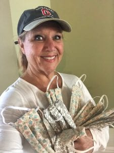Debbie Turner smiles while holding several fabric face masks.