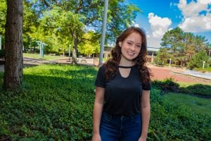 Paige Dillen stands outside on campus