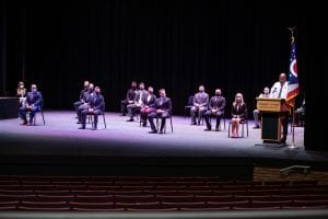 Cadets sit socially distanced on the stage of the Hoke Theatre