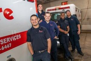 Five paramedics stand with ambulances.