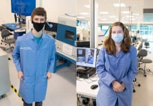 Two students in blue lab coats and masks
