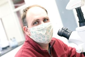 Man wearing a face mask sitting at microscope