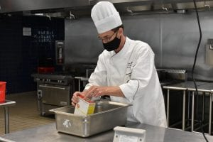 Chef Stephen Hahn in white coat and chef hat