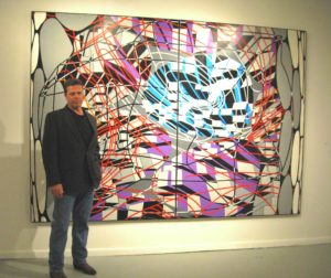 A picture of James Massena standing in front of his artwork