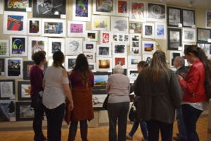 Group of people viewing wall filled with student paintings and drawings