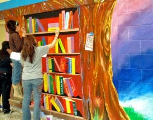 Painting of bookshelf on wall as teacher reaches for book