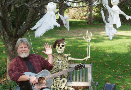 Lee Murdock sitting under a tree on a wooden bench next to a waving skeleton. Ghost decorations hang from tree branches