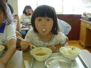 Child using chopsticks and playfully showing food in her mouth. Photo by Donna Shurr