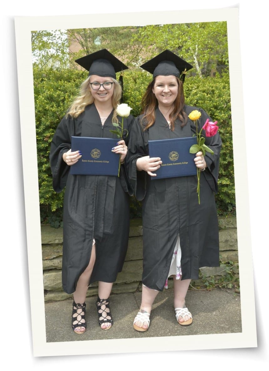 Two young ladies in graduation caps and gowns holding LCCC diplomas and flowers