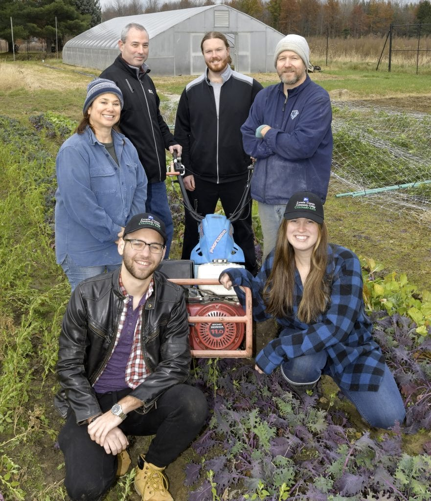 Group of people standing in a farm field. Chef Adam Schmith, Chef Brad Ball, Coleman Gardens owners Marcia and Eric Coleman, LCCC Culinary Arts students Cameron Howell and Kirsten Gowin