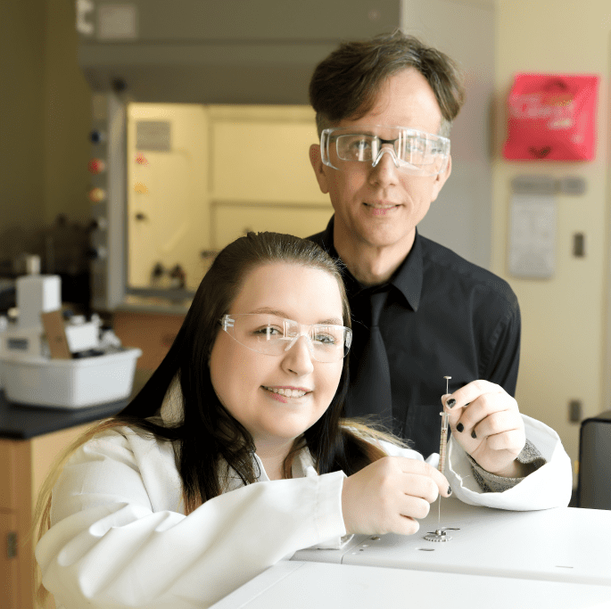 Heather Ketchum and Regan Silvestri - young woman in a lab coat and safety glasses beside her professor using lab equipment in a science lab