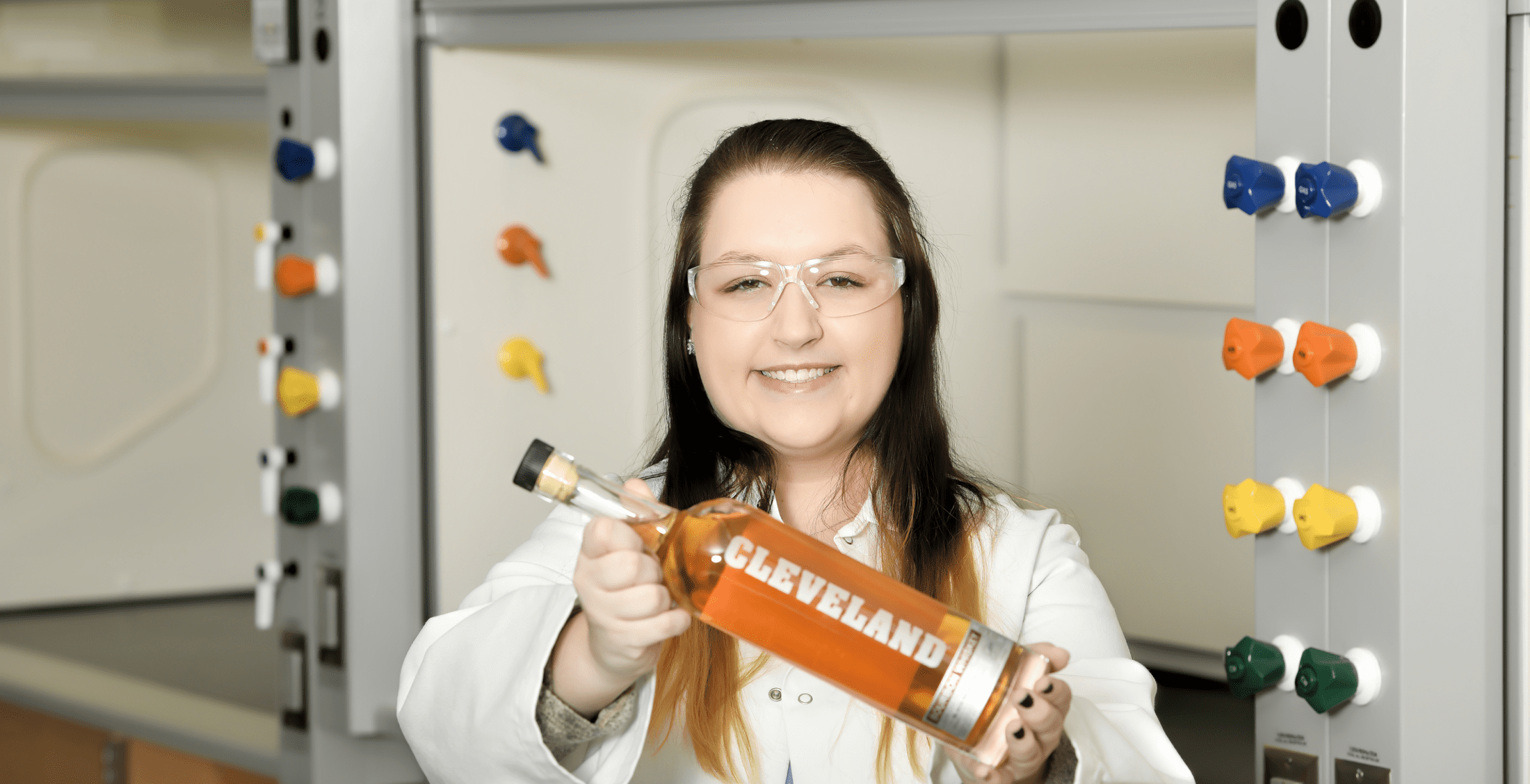 Heather Ketchum - young woman in a lab coat holding a bottle of whiskey