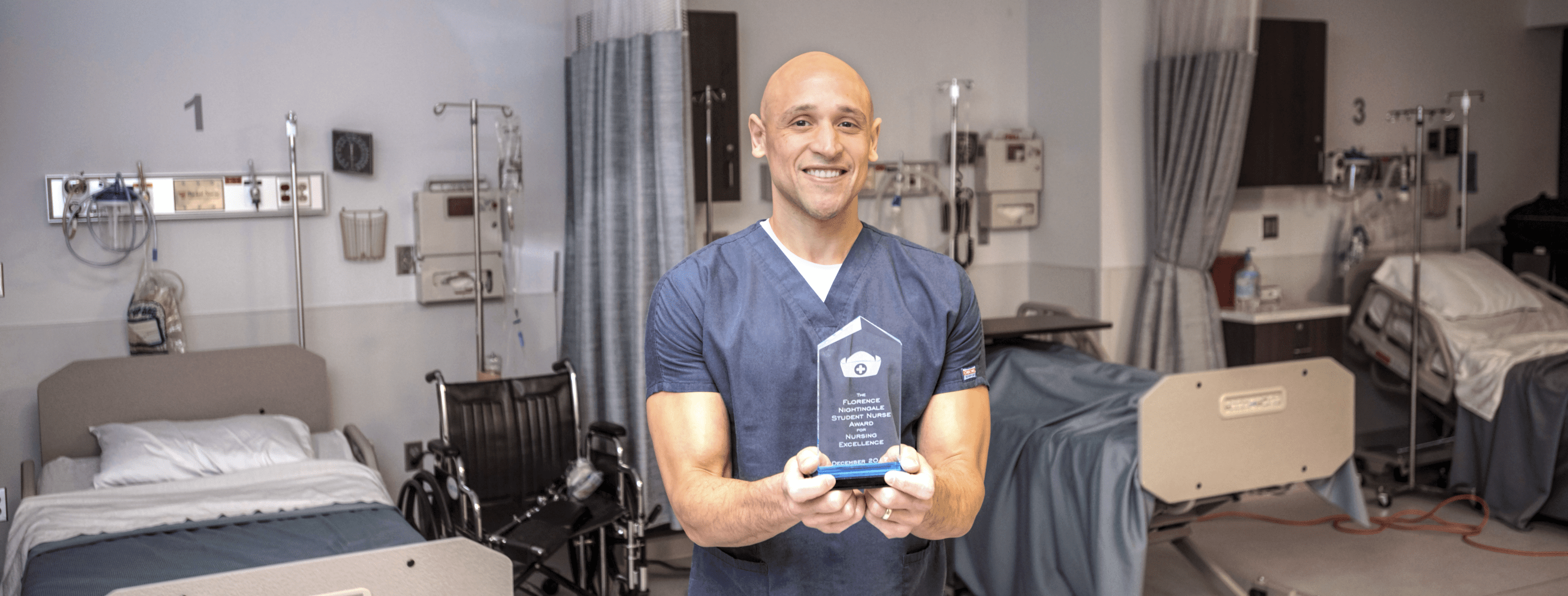 Jimmy Lopez - man in medical scrubs holding a glass award