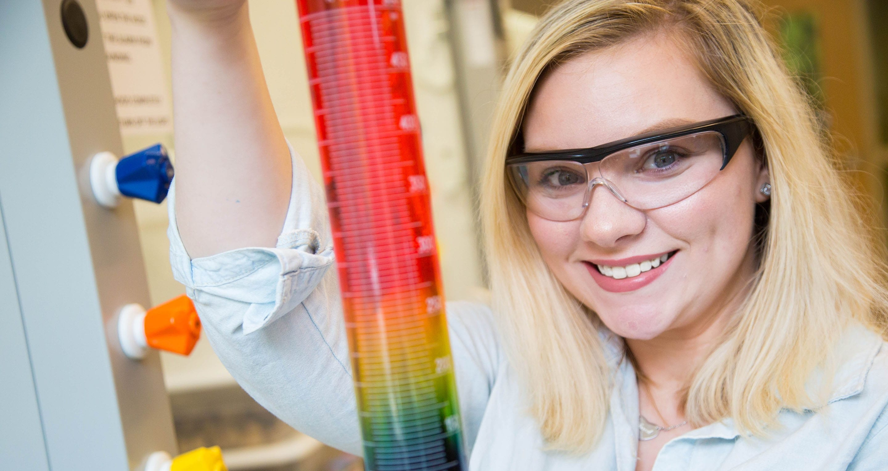 Mikayla Stephans - Young woman holding science equipment wearing safety glasses