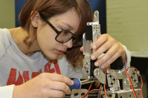 School-aged girl working on robotic equipment