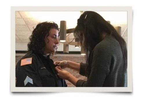 Tabitha Angello's daughter, Brianna Cirilo, pins on her mother's new badge