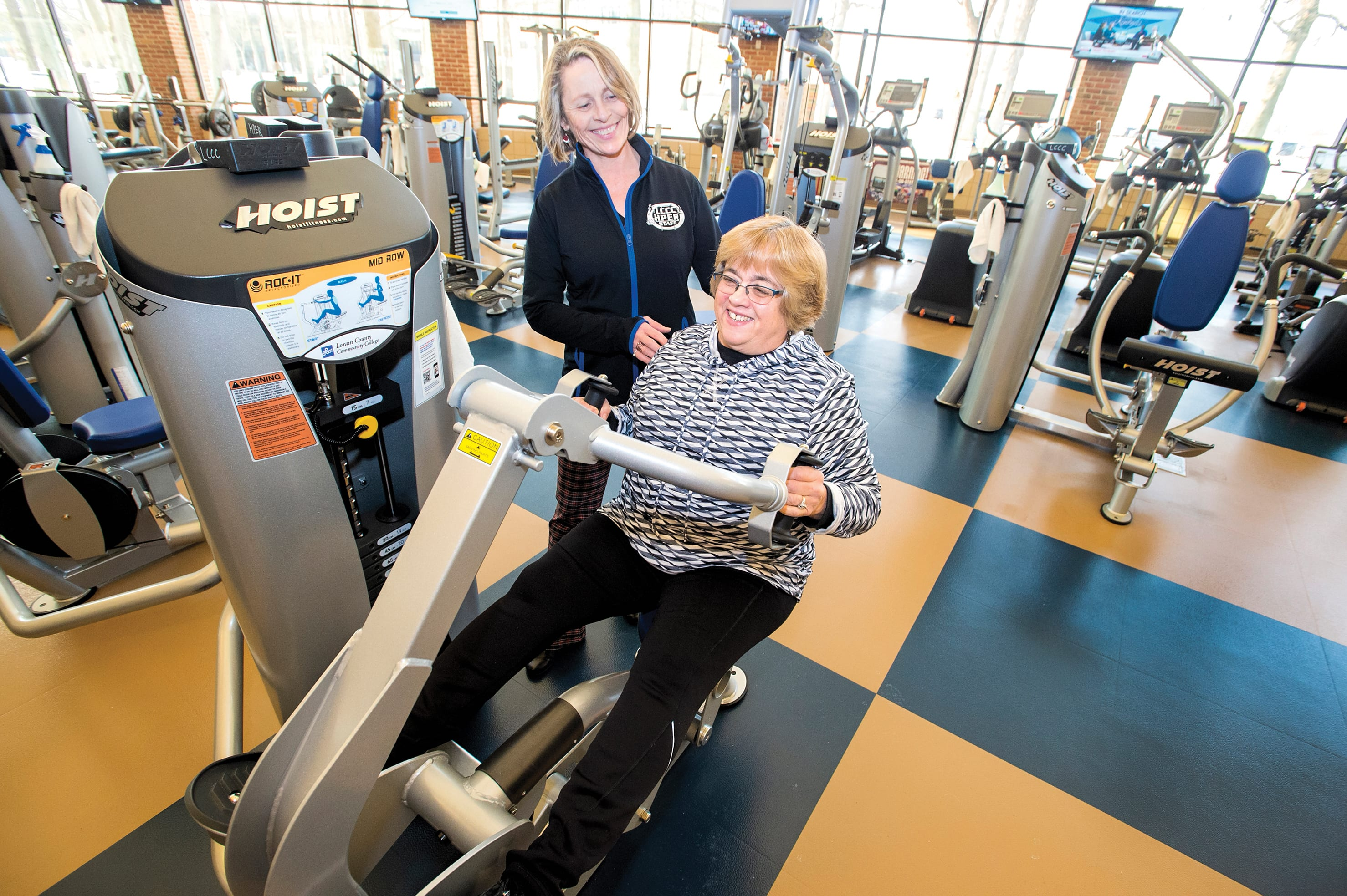 Phaidra Cox in the fitness center with trainer Kathryn Orantek