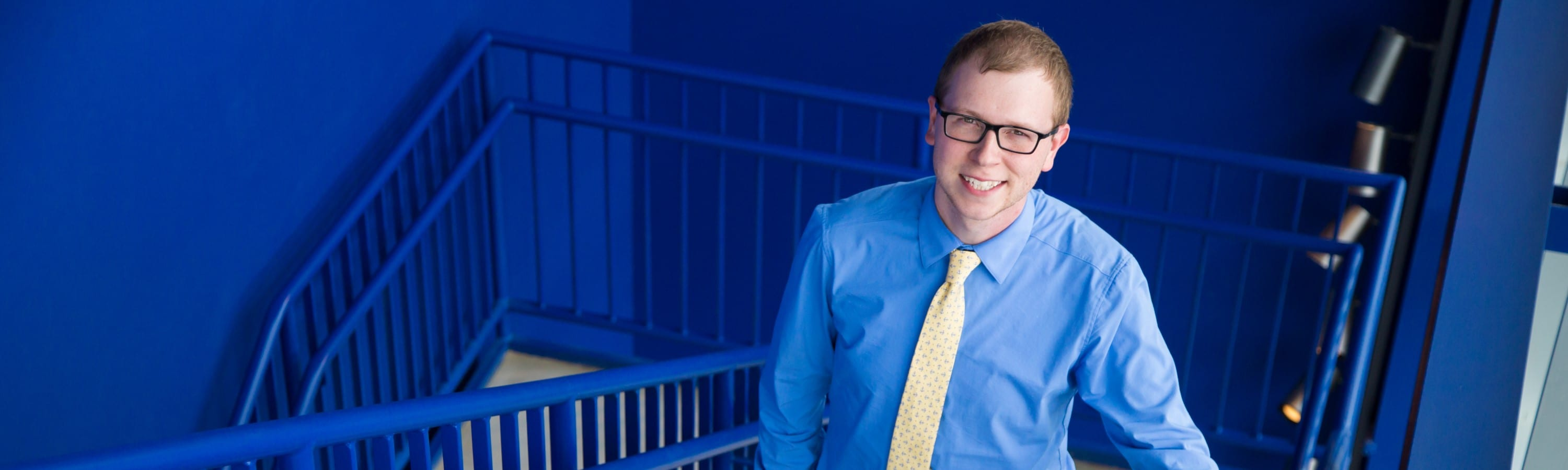 Young Professional standing in a blue stairwell.